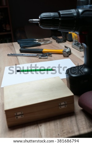 Pen and blank piece of paper on wooden table with working tools in carpentry workshop