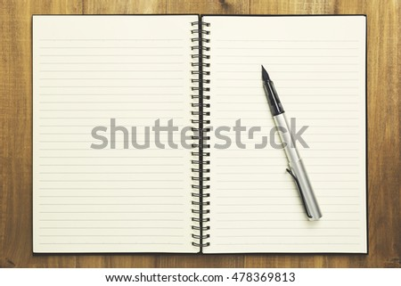 Pen and Books on wood table background,  top view