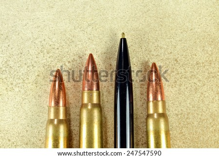 Pen and bullets as conceptual expression of the power of words - stock photo