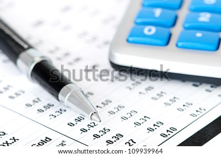 pen and calculator on business paper background - stock photo