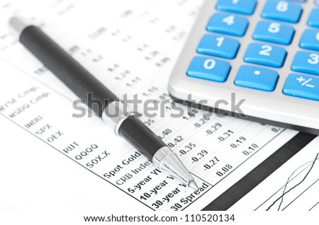pen and calculator on business paper background