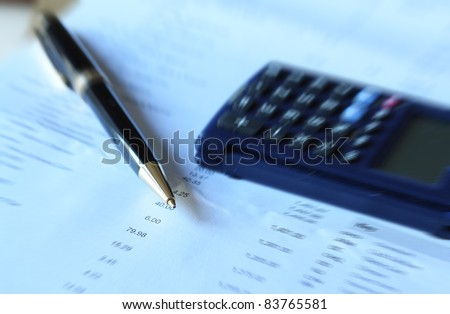 Pen and calculator on financial document - radial blur technique used - stock photo