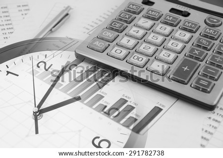 pen and calculator on financial documents and clock - stock photo