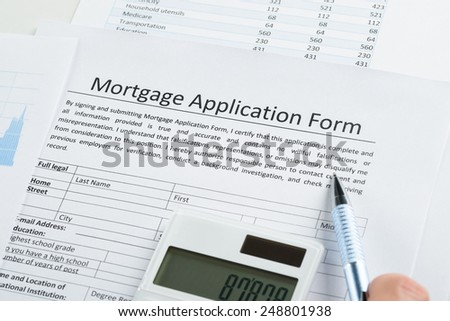 Pen And Calculator On Mortgage Application Form
