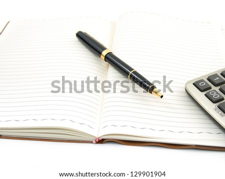 Pen and calculator on notebook - stock photo
