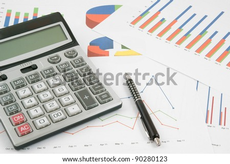 Pen and calculator on paper table with diagram