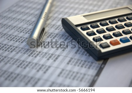pen and calculator on the paper tables