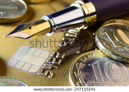pen and coins on a credit card close-up