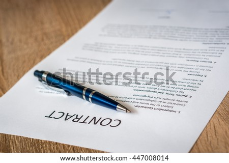 Pen and contract paper on the wooden table - stock photo