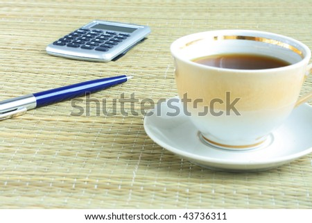 pen and cup of coffee on the table