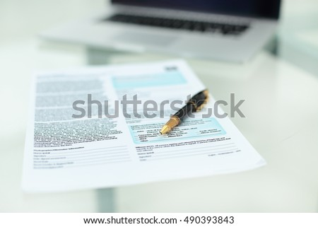 Pen and documents close on a glass desk