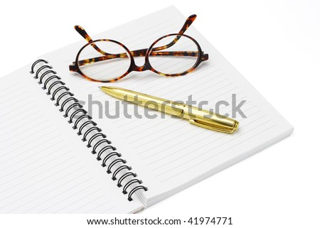 Pen and eyeglasses on a notebook on white background - stock photo