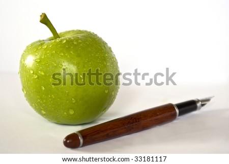 Pen and fresh green apple - stock photo