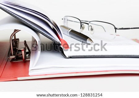 Pen and glasses on an opened diary - stock photo