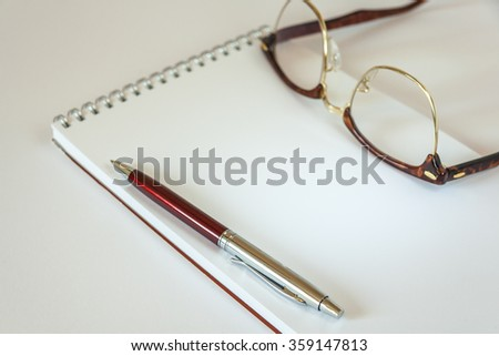 Pen And Glasses On Notepad