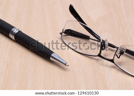 pen and glasses on wood table