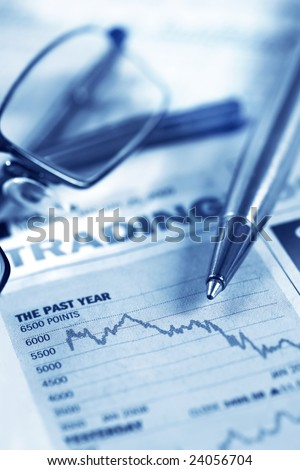 Pen and glasses over stock performance graph.  Depressing results!  Blue toned image. - stock photo