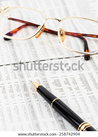 Pen and glasses rest on stock price detail financial newspaper