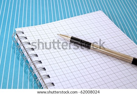 Pen and graph paper notebook on a blue lined tabletop