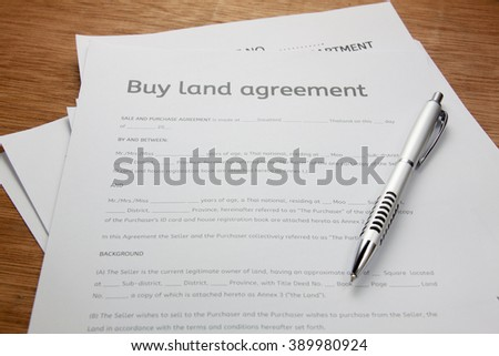 pen and land contract form on wood background.Business buy and sell home concept. - stock photo