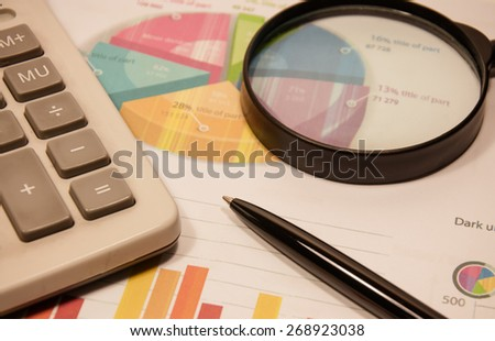 pen and magnifier with graphs analysis on table. - stock photo