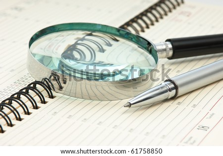 pen and magnifying glass on the calendar - stock photo