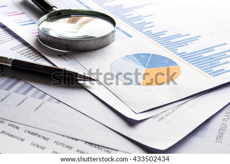 Pen and magnifying on financial graph chart.For business concept. - stock photo