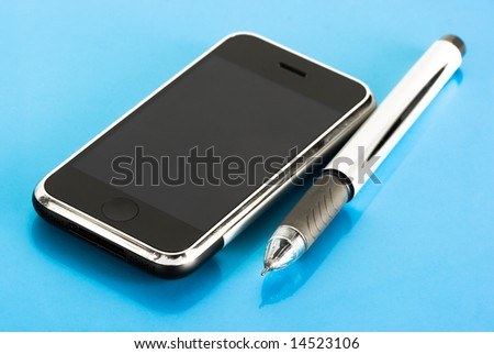 pen and mobile phone on blue background - stock photo