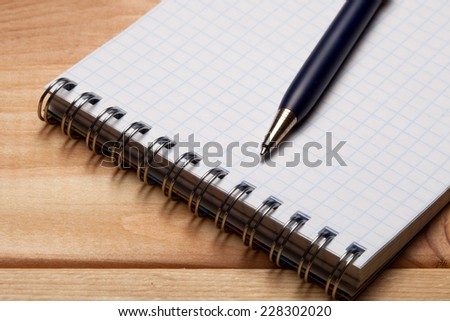 Pen and notebook on wooden table.  - stock photo