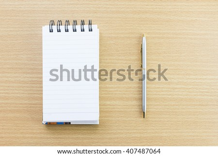 Pen and open notepad with blank page on wood table - stock photo