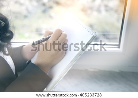 pen and paper hand woman in window
