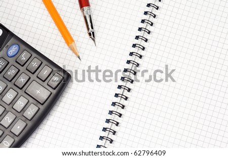 pen and pencil on checked notebook with calculator