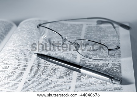 pen and reading glasses with books open
