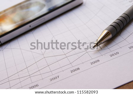 Pen and smartphone on Financial Chart with positive growth pattern