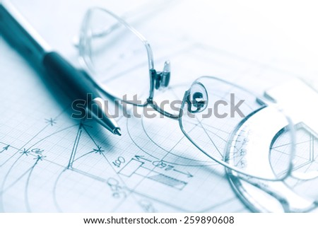 Pen and spectacles near ruler on graph paper with chart - stock photo