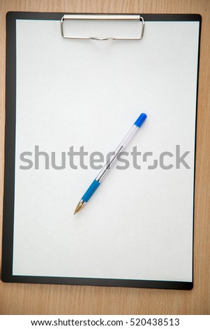 pen and tablet with a sheet of paper on the table