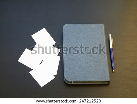 pen and white paper and workbook on a black background. - stock photo