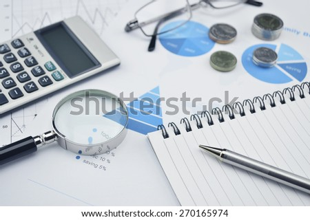 Pen book glasses magnifying glass and calculator on financial chart and graph, accounting background - stock photo