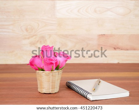 Pen, brown notebook and pink rose flower in the basket on wood background