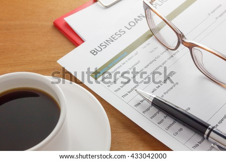 pen,Business loan application form,coffee,glasses,paper clip on wood business background.