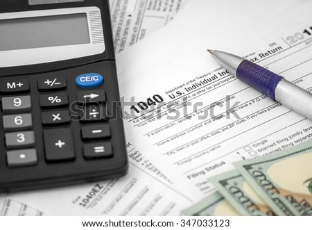 Pen, calculator and dollars on Tax Forms 1040