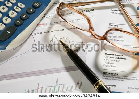 Pen, eyeglasses and calculator over business-stock report