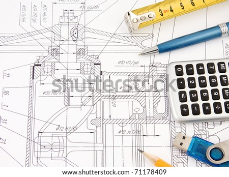 pen, flash memory and tape measure on drafting