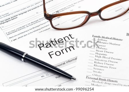 Pen, Glasses and Patient Form on desktop in business office. - stock photo