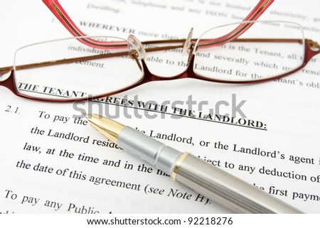 pen,glasses and tenant agreement with the landlord