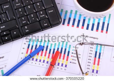 Pen, glasses, computer keyboard and cup of coffee on financial chart, business concept, analysis of sales plan, business report, business work station with paperwork - stock photo