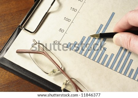 Pen in hand pointing at a bar graph on a clipboard with glasses. - stock photo