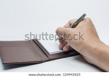 pen in hand writing on the notebook  isolated on white