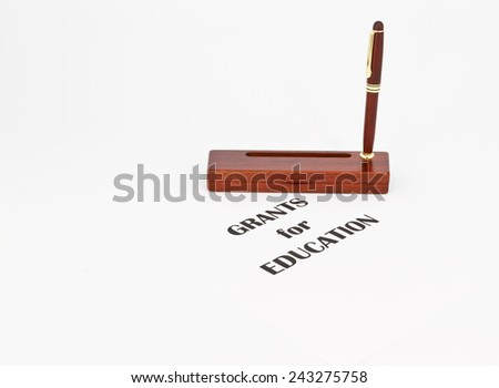 """Pen in rosewood stand in front of """"Grants for Education"""" reflects writing proposals to fund schools and educational costs. Copy space available. - stock photo"""