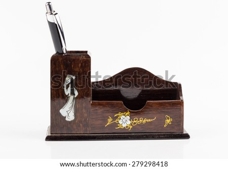pen in wooden box on white background